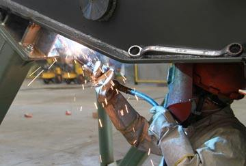 a worker is welding the equipment